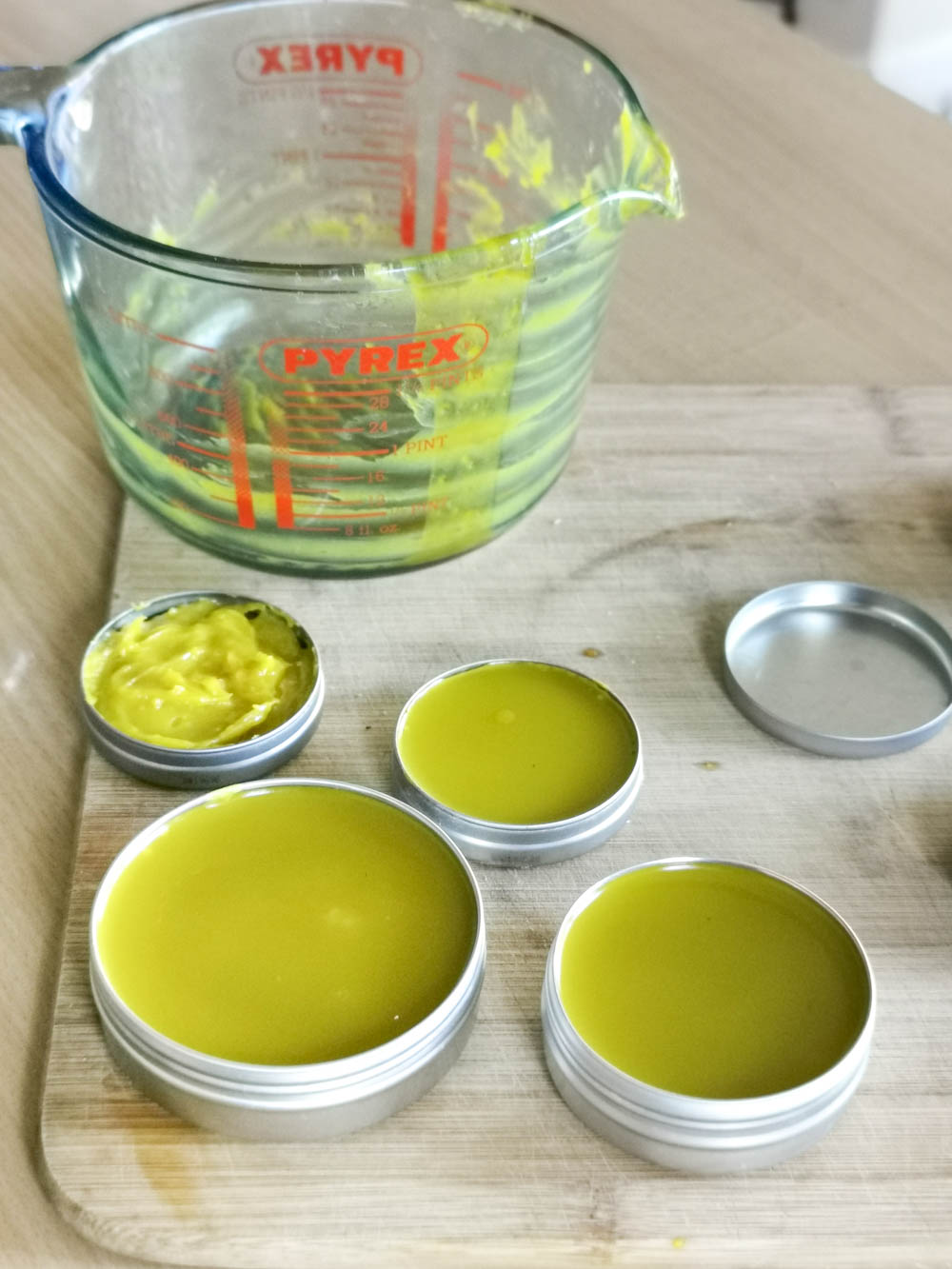 Calendula salve being poured into recycled tins.