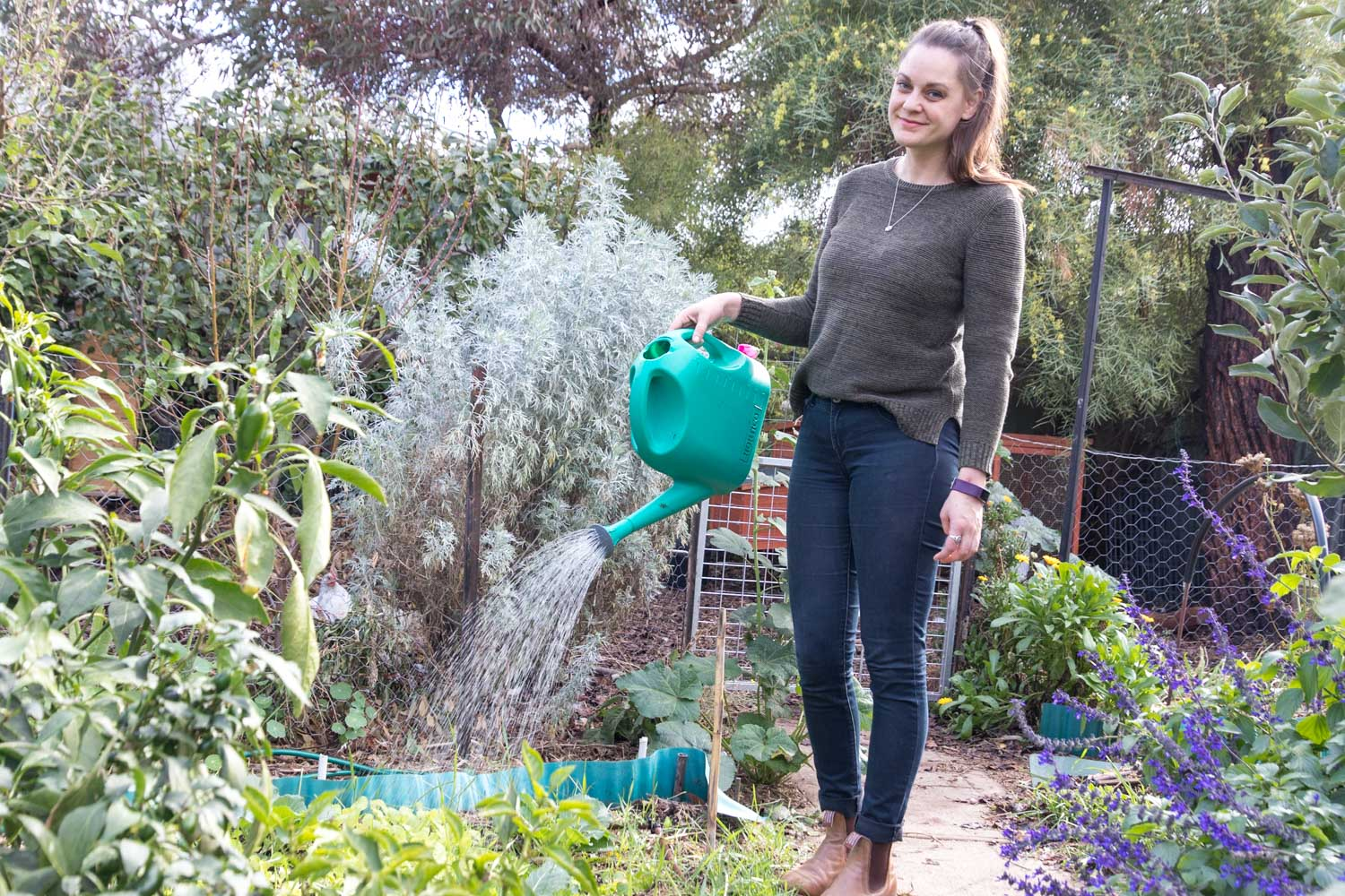 Me fertilising my garden with a green watering can and homemade weed tea.